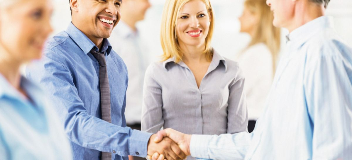 two men shaking hands discussing Two Rivers Insurance Business Insurance Products and smiling. A woman stands smiling next to the men.